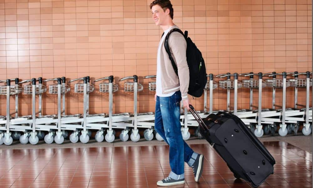 man carrying travel backpack
