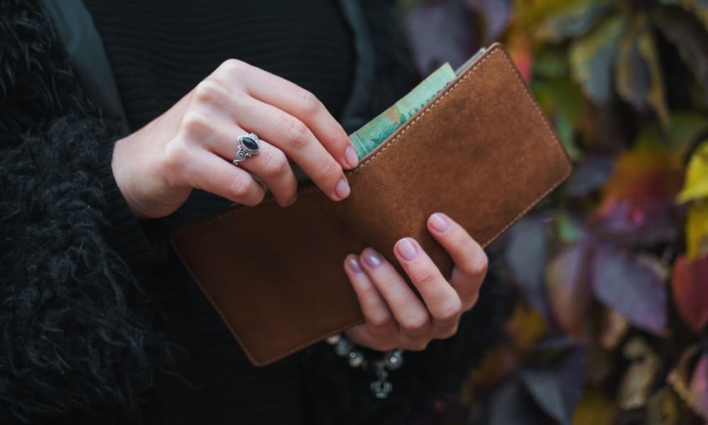 getting money out of a brown leather wallet